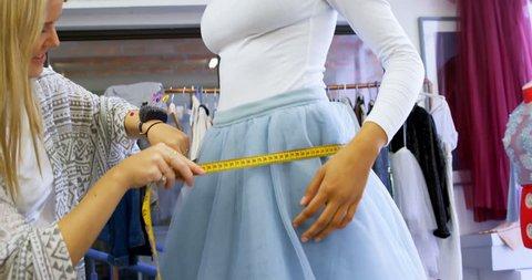 Fashion designer taking measurement of customer in fashion studio