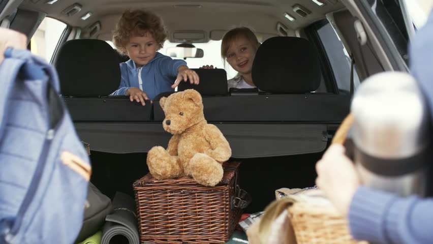 Medium shot of excited curly little boy with plush toy and cheerful girl sitting in backseat of family car and talking to parents putting picnic essentials in trunk before going on trip