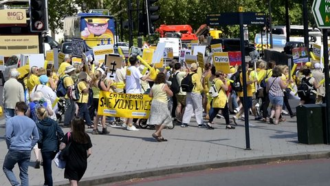 London, UK - June 22, 2018: High angle view on people holding up signs at Cystic Fibrosis protest in England to make Orkambi medicine drug free, yellow color clothes, marching, walking