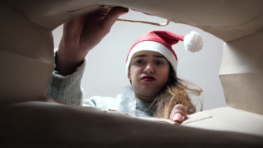 Slow motion of young disappointed woman in Santa Claus hat opening bag with Christmas presents. Bottom angle. Woman frustrated with the gifts. | Shutterstock HD Video #1018121881