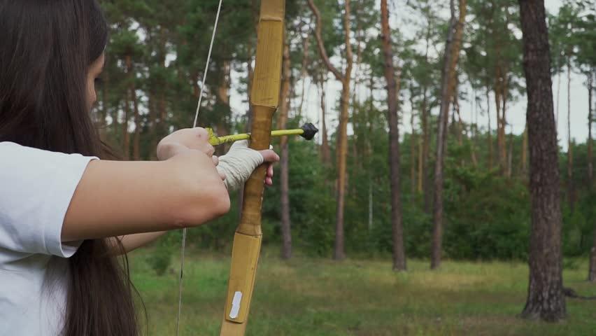 Young girl draving arrow and shooting target #1018126681