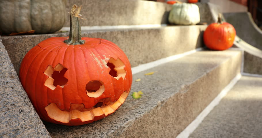 A scary carved pumpkin Jack o Lantern on the steps of a home before Halloween trick or treat   Shutterstock HD Video #1018136281