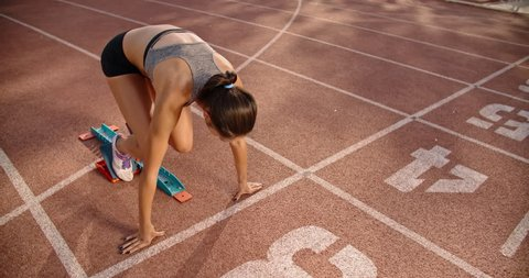 Female athlete on track. Young south asian athlete standing on start on stadium, then rushing forward, getting ready for competition 4k