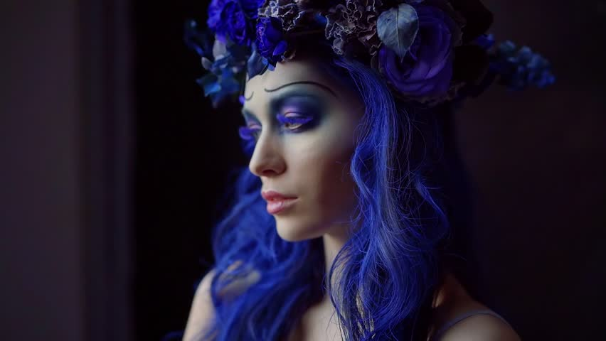 Halloween face art. Portrait of beautiful woman with Halloween makeup corpse bride. Blue accents on hair and eyes, black background   Shutterstock HD Video #1018171771
