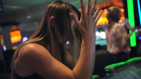 This video shows a young caucasian woman disappointed as she loses money on slot machines while gambling at a casino.