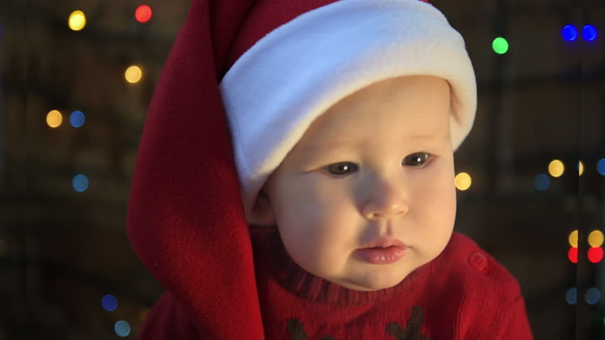 Cute little child in Santa hat over Christmas lights background. New Year celebration concept.  | Shutterstock HD Video #1018172251