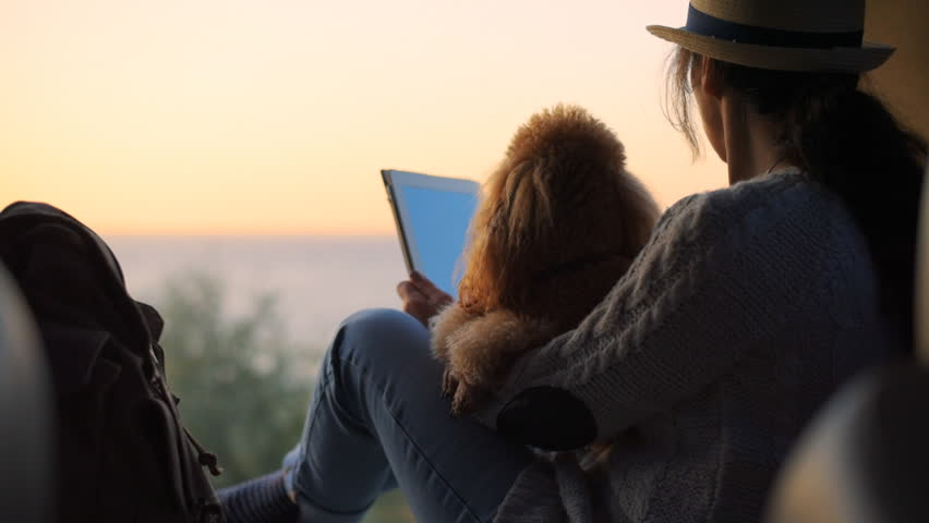 Woman traveler is holding touch pad, while is relaxing outdoors during his trip on the sea. Woman is traveling with her dog. | Shutterstock HD Video #1018178731