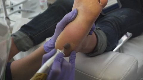 Pedicure dead skin remover foot rasp woman. The process of creating a pedicure. Beauty and pedicure salon. Hardware pedicure.