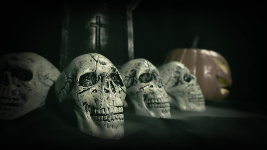 Old film look of halloween set decoration with skulls, grave and jack o'lantern   Shutterstock HD Video #1018184701