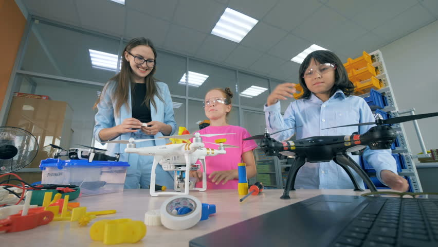 School kids explore drones, copters at technology class.   Shutterstock HD Video #1018188391