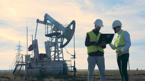 Two workers standing on an oilfield near oil pumps.