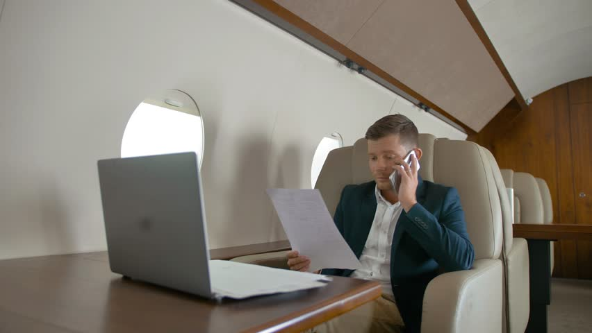 Rich business man talking by mobile phone partner connection aircraft jet travel and work on laptop on luxury expensive table. Middle shot in slow motion. | Shutterstock HD Video #1018189801