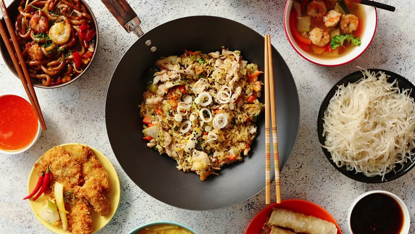 Chinese food set. Chinese noodles, fried rice with chicken, tom yum soup, spring rolls, deep fried fish and udon. Top view. Asian style food concept composition.   Shutterstock HD Video #1018208071