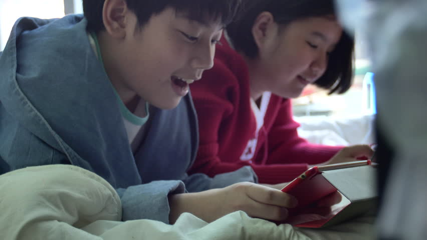 Slow motion of Happy asian boy and girl playing game on tablet computer together with smile face. 4K