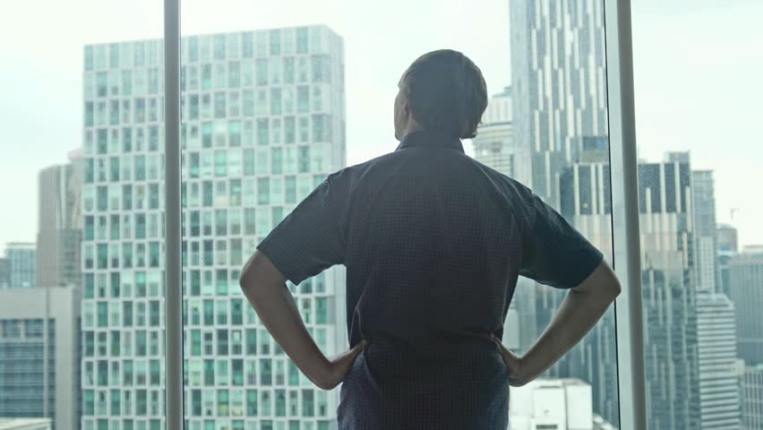 Young successful rich man comes to the window and admire the city center with skyscrapers view. 3840x2160 | Shutterstock HD Video #1018237861
