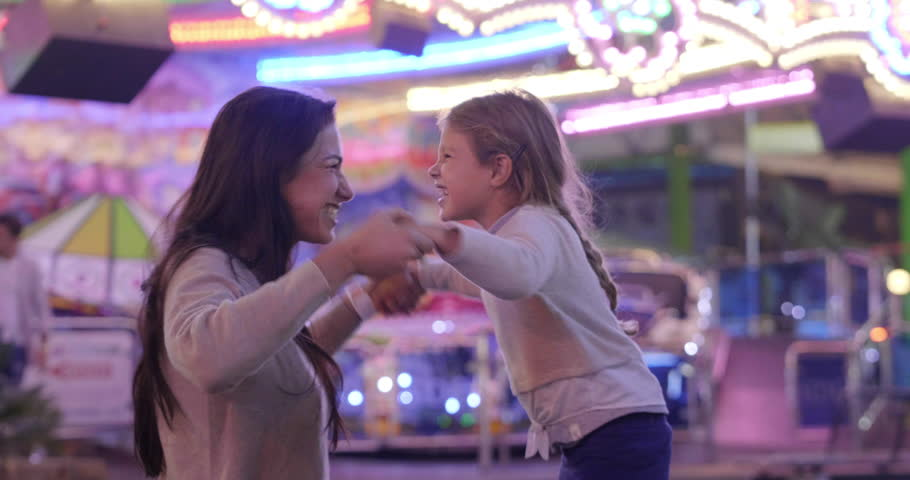 Portrait of a young mother smiling and having fun with her daughter at the Luna Park. Concept: Happiness, freedom, fun, family | Shutterstock HD Video #1018241041