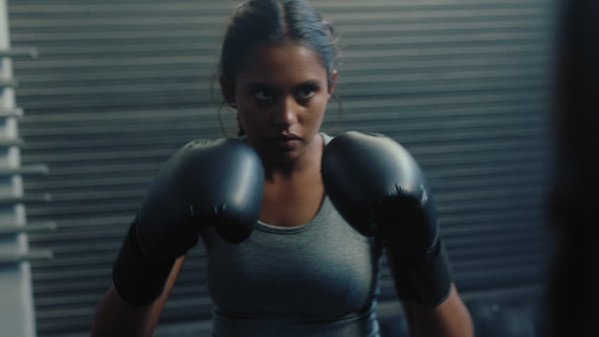 Woman athlete training kickboxing exercise workout punching bag tough female fighter practice boxing in gym enjoying fitness lifestyle | Shutterstock HD Video #1018250551