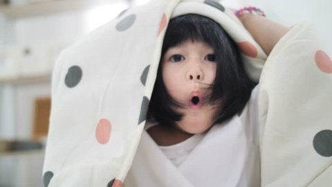 4K Slow motion of Cute little Asian girl covers with blanket. Playing hide and seek, peek a boo