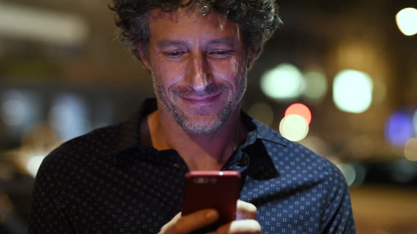 Smiling man using smart phone during night looking at camera. Closeup face of happy mature businessman messaging on cellphone at night on the street with the lights of the road blurred in the backgrou