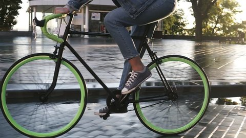 Close up footage of female feet cycling a bicycle in the morning by paved city street with wet asphalt . Side view of a young woman riding a trekking bike with green wheels, wearing sneakers and jeans