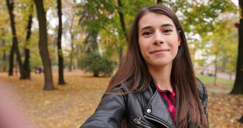 Female student in the park. Charming girl in leather jacket walks around autumn park and films herself on the camera