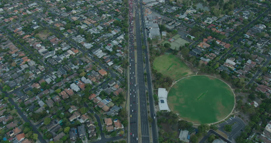 Aerial sunrise view commuter vehicles travelling along Nepean Highway past residential houses and Hurlingham Park Brighton Melbourne Australia | Shutterstock HD Video #1018444591