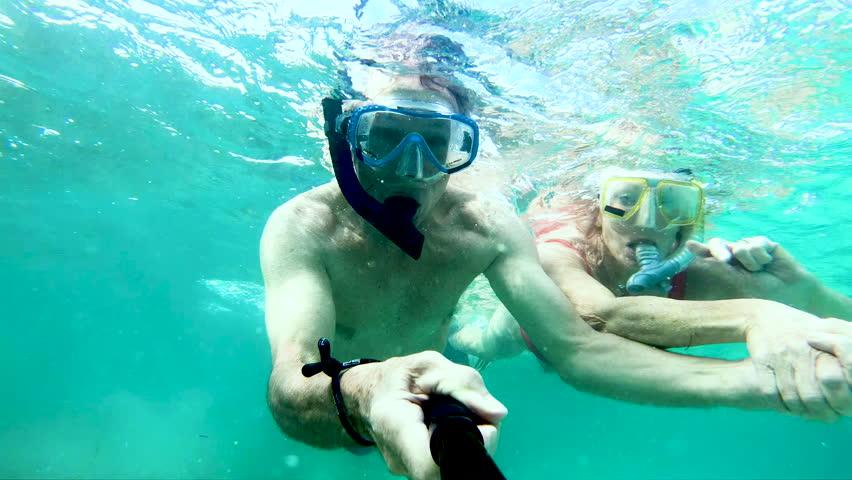 Selfie portrait of active senior Caucasian American couple snorkeling waving to camera making video diary and enjoying Summer adventure Bahamas USA | Shutterstock HD Video #1018447231