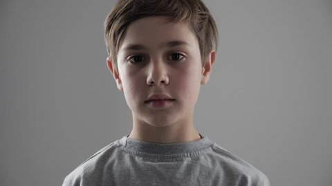Portrait of cute young 11 - 12 year old boy looking at the camera on white background