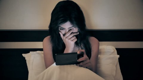 A young and beautiful woman sitting on bed and watching an action or thriller movie on a mobile phone. An attractive girl covering her face while watching a horror film on smartphone or cellphone.
