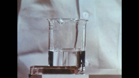 "1960s: Lab. Man drops piece of copper into beaker. Liquid fizzes and forms smoke. Molecule labelled ""NITRATE ION"" next to chart. Man drops piece of zinc into liquid."