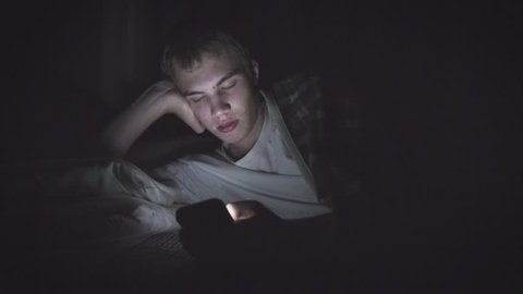 Bored teenager lying on his bed in the dark while scrolling through his phone. The light from the phone is illuminating his face.