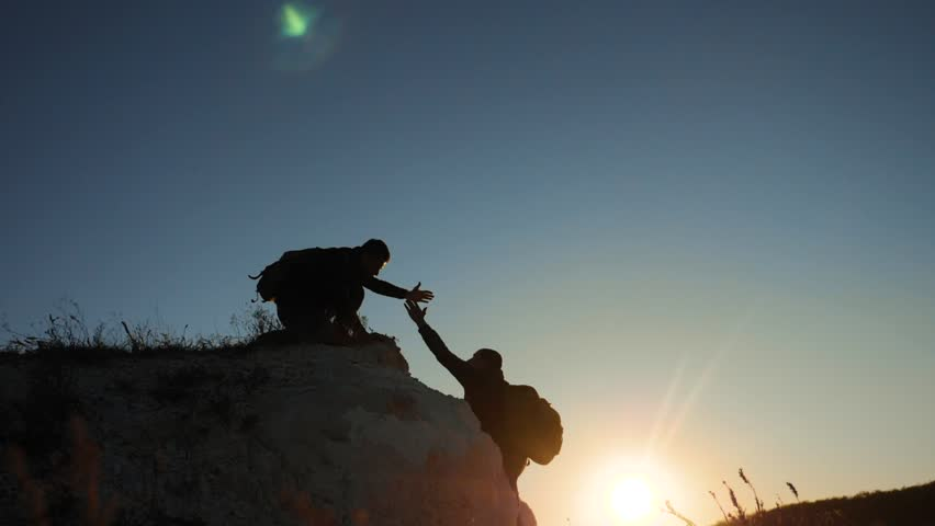 Silhouette two men teamwork tourists climber climbs a mountain. walking tourist hiking adventure climbers sunset climb the mountain . slow motion video. hiker sunlight on top win victory the hill | Shutterstock HD Video #1018583701