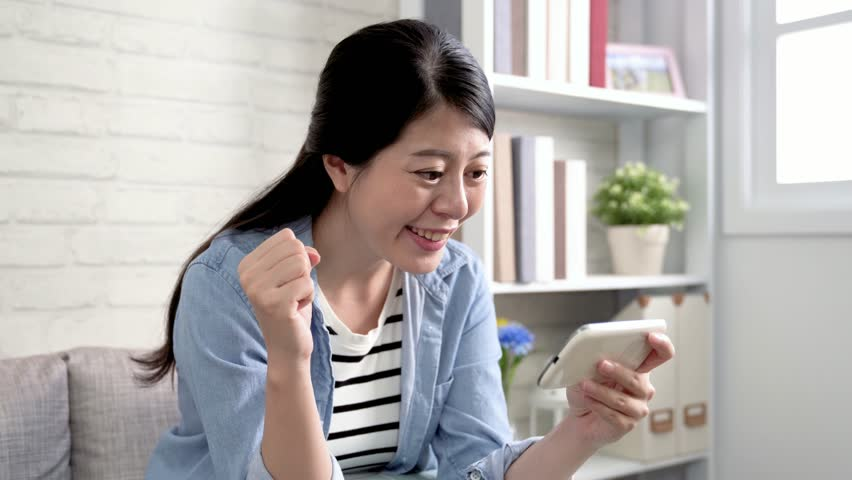 Happy female supporter watching football on smartphone with online sport subscription. Crazy fan celebrating a goal in world soccer game. asian woman fun hobby lifestyle concept. | Shutterstock HD Video #1018585531
