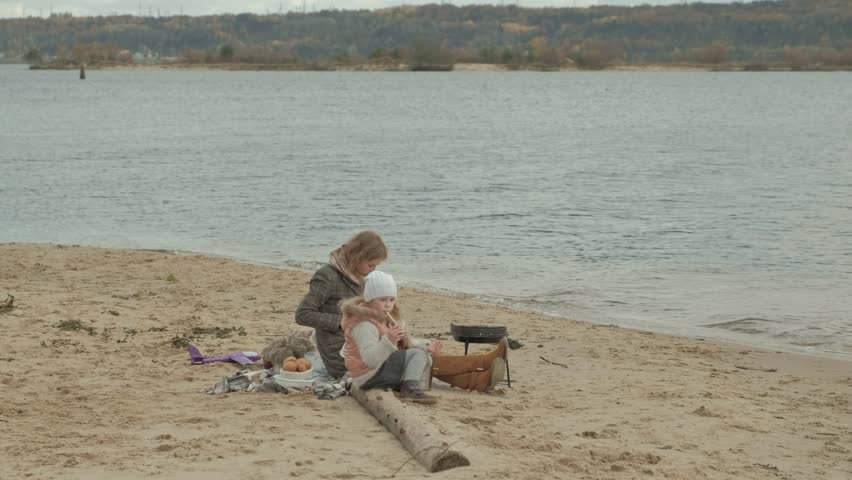 Young woman in a coat with a girl with curly hair, mom and daughter, sitting on the beach by the river, ocean, having a picnic, drinking hot tea, cutting vegetables, cold weather 4k | Shutterstock HD Video #1018596661