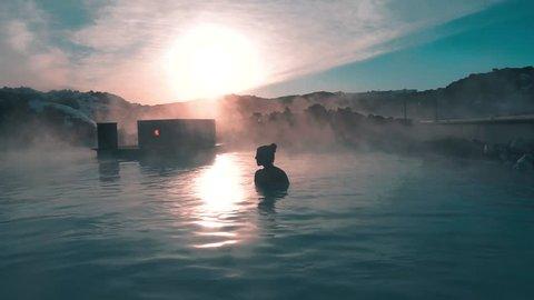 Girl enjoying the Blue Lagoon hot spring at sunset