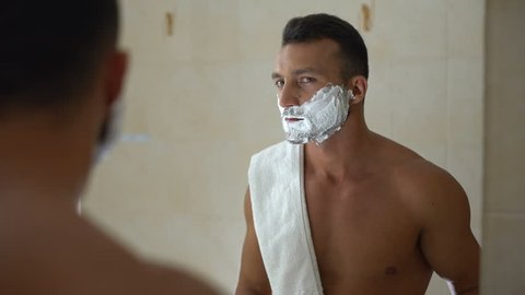 Male with foam on face using manual razor to trim and shave beard in bathroom