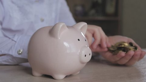 Happy girl save money in piggy bank in her home. Child inserting a coin into a piggy bank, indoor financial concept. Kid saving money for future concept.