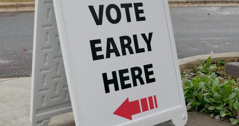 Vote early here sandwich board sign with an arrow pointing to the left to the voting location