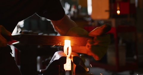 Professional male blacksmith forming red hot metal on an anvil in interior blacksmith workshop in dark day lighting. Close up on 4k RED camera.