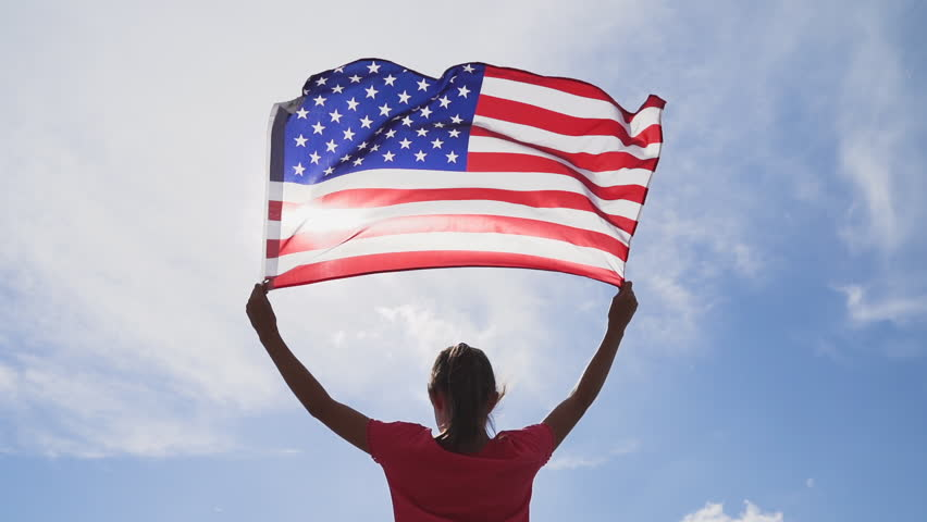 Child girl is waving American USA flag on top of mountain at sky background. Footage in slow motion | Shutterstock HD Video #1018698121