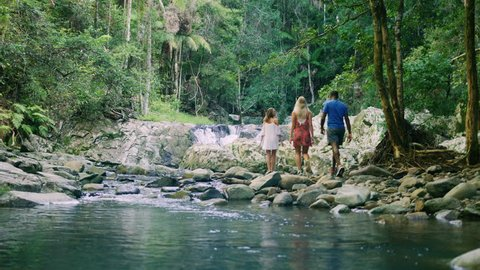 Three young ethnically diverse friends walk along the rocky bank of a stream in an Australian forest in natural sunlight. Wide shot, in 4K on a RED camera.