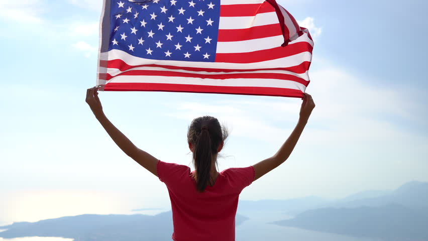 Child girl is waving American USA flag on top of mountain at sky background. 4K | Shutterstock HD Video #1018732291