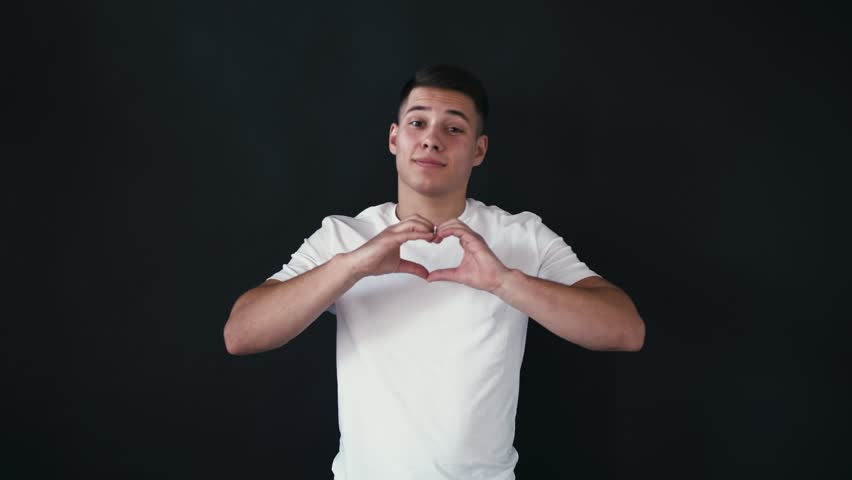Lovely and handsome young man sends kisses to camera and shows heart shape with fingers. He is very confident. Young man shakes his head and still looks on camera. Isolated on black background
