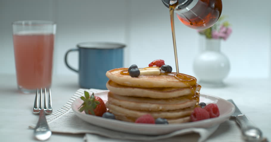 Bottle of maple syrup being poured over a stack of delicious plate of pancakes on a table, with soft interior lighting. Close up slow motion shot on 4k PHANTOM FLEX camera. | Shutterstock HD Video #1018756351