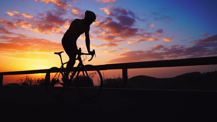Silhouette of a man riding a Bicycle at sunset on a mountain road side view. Slow motion steadicam #1018822291