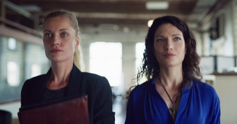 Two focused business women professionals walk silently down hallway in hipster industrial office during the daytime. Wide to medium shot on 4K RED on a gimbal.
