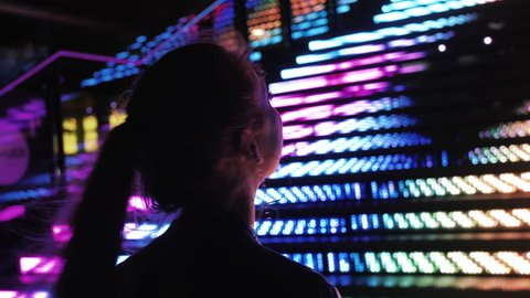 Young Beautiful Woman Standing Beside Neon RGB Lights, Nightlife. Young Woman Taking in the City at Night, Long Hair Side Profile Silhouetted