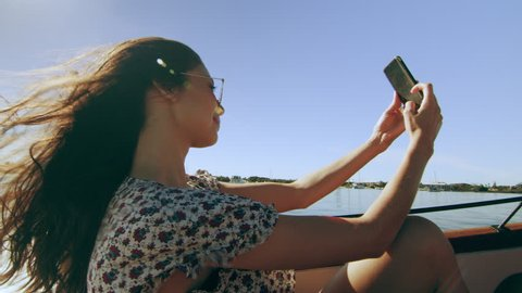 Beautiful young woman wearing sunglasses cruising on a motorboat, wind in her hair, taking selfies, near the beach under a sunny blue sky. Medium shot on 4K RED camera with lens flare.