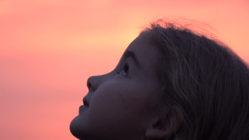 Kid looking up at the sky in nature. Little girl praying looking up at purple sky with hope, close-up.  | Shutterstock HD Video #1018841071