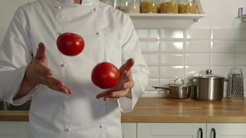 Chief-cooker juggles a red tomatoes in a kitchen - Slow motion